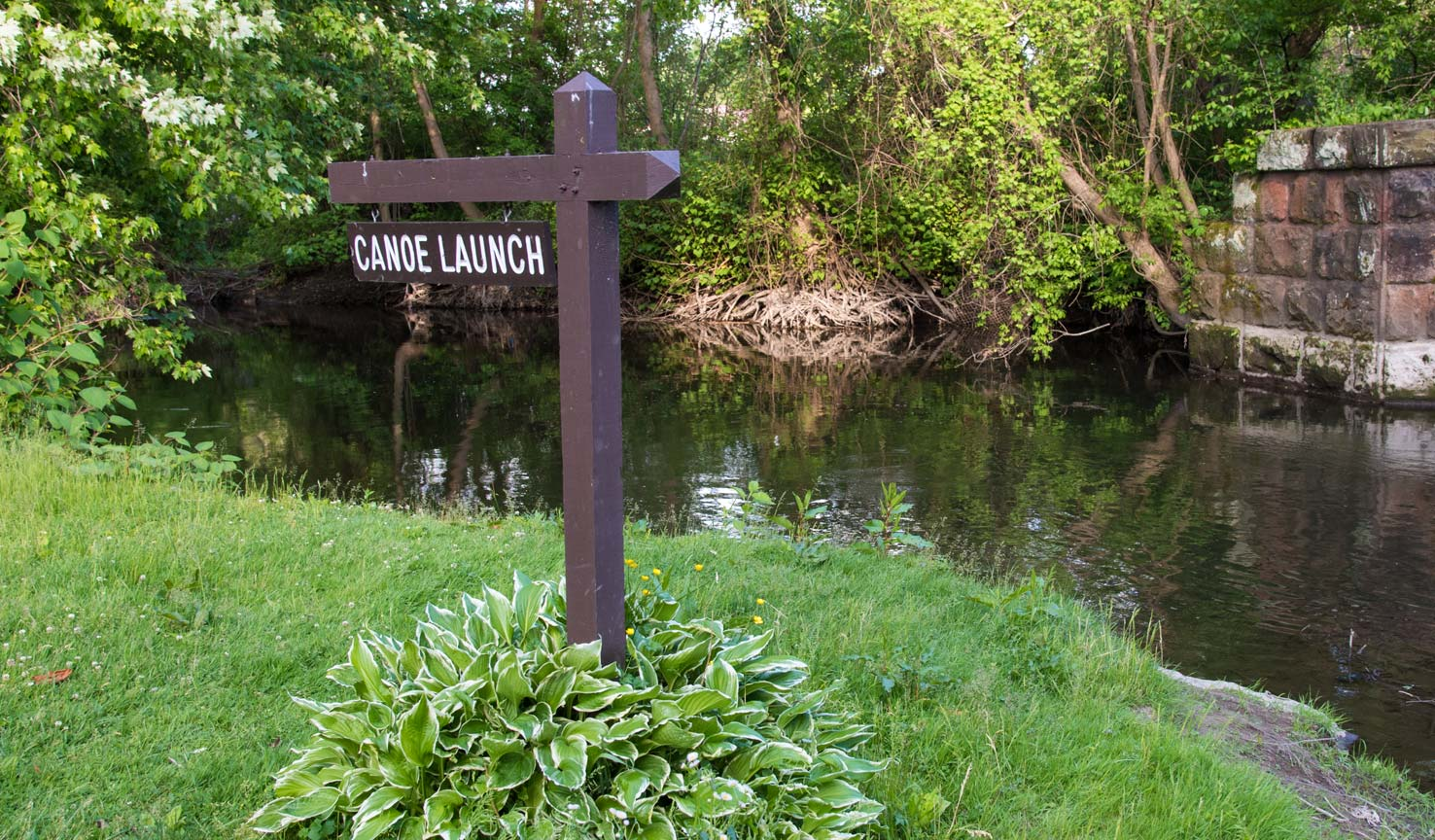 A sign in front of a creek with the words 'canoe launch'